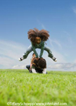 Multi-ethnic children in a large green field playing leap frog and having fun